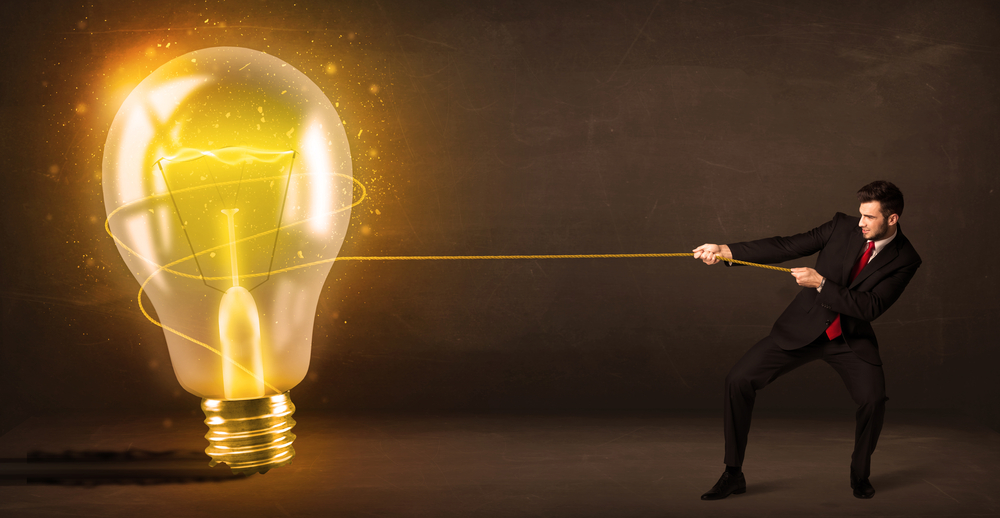 Business man pulling a big bright glowing light bulb concept on background