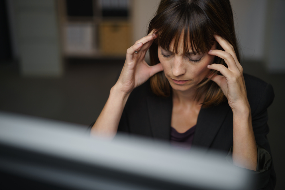 Businesswoman suffering from a headache or migraine holding her hands to her throbbing temples as she works late in the office to a deadline