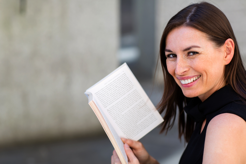 Happy woman enjoying reading a book outdoors
