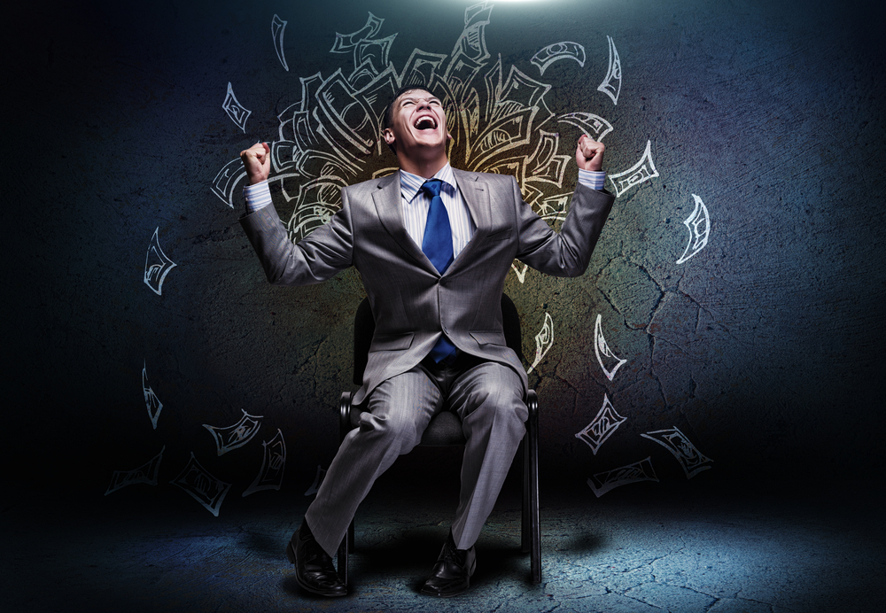 Joyful businessman sitting on chair under money rain